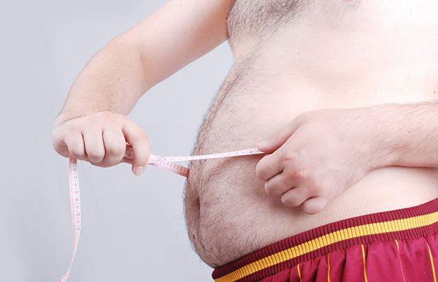 Un gros homme mesurant la taille