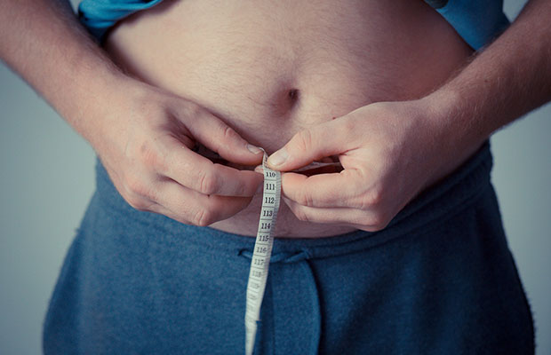 homme mesurant la graisse du ventre