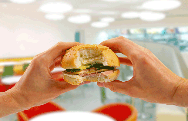 mains tiennent un hamburger dans un restaurant fast-food