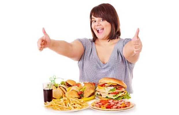 les femmes en surpoids avec des assiettes de nourriture