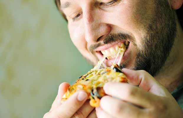 jeune homme manger de la pizza