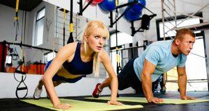 Couple faisant des flexions dans la salle de gym