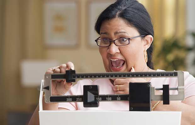 Femme en surpoids sur une échelle de poids